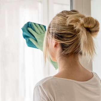 Back view of woman cleaning window with cloth