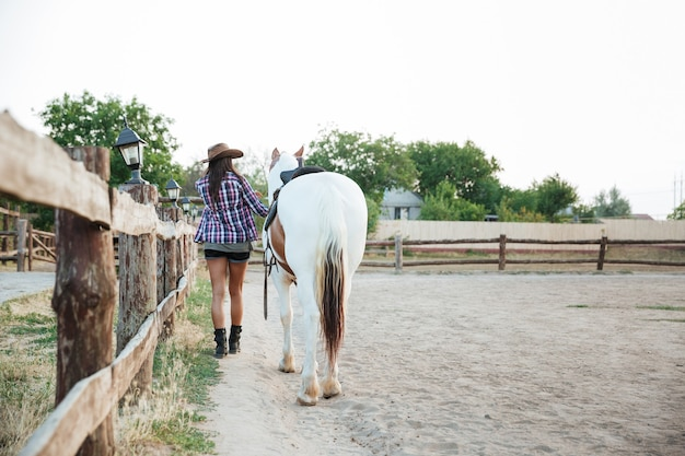 Back view of woman cowgirl walking with horse in village