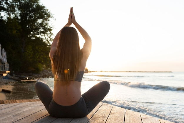 Donna di vista posteriore che fa yoga sulla spiaggia