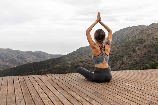 Back view of woman doing yoga outdoors with copy space