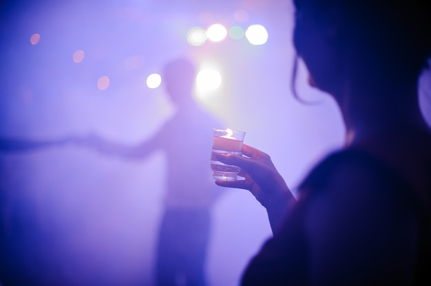 Back view of woman drinking shot in night club