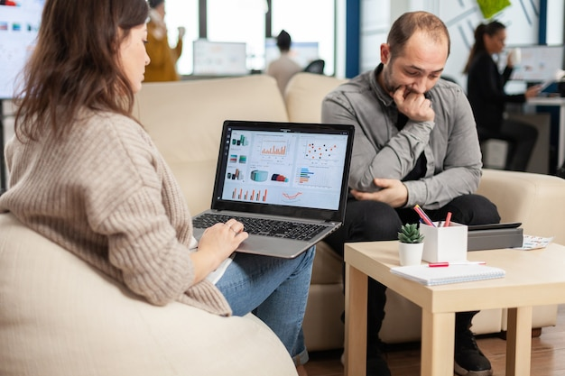 Back view of woman entrepreneur sitting on couch in office using laptop computer while colleagues working on background. multiethnic coworkers planning new financial project in modern company