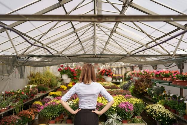 Vista posteriore della donna imprenditrice guardando il risultato del suo lavoro. proprietario di una serra guardando diverse specie di fiori