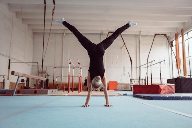 体操オリンピックのために運動している背面図の女性
