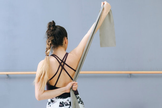 Back view woman exercising with elastic band