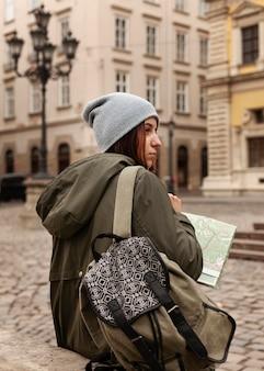 地図を保持している背面図の女性