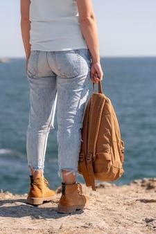 Donna di vista posteriore che tiene uno zaino sulla spiaggia