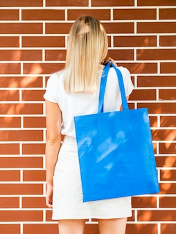 Back view woman holding a blue bag