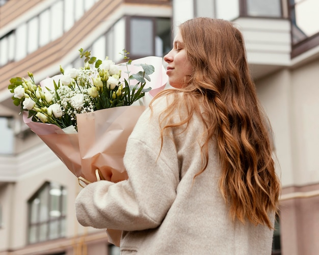 Back view of woman holding bouquet of flowers outdoors