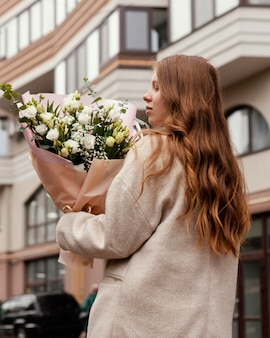 Back view of woman holding bouquet of flowers outside
