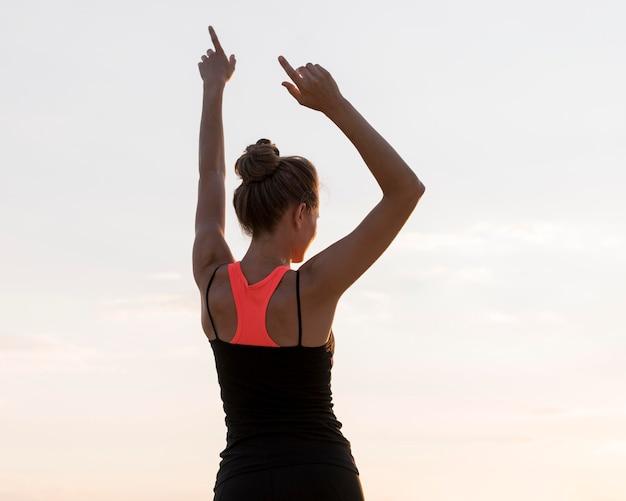 Вид сзади женщина, держащая руки вверх