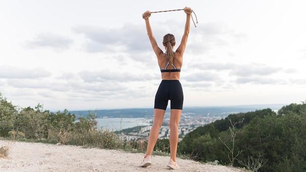 Donna di vista posteriore che tiene una corda in su