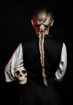 Back view of woman holding skull