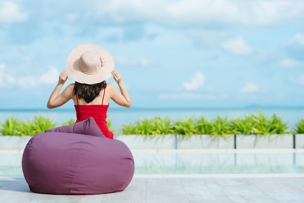 Back view of woman holding straw hat relaxing by swimming pool