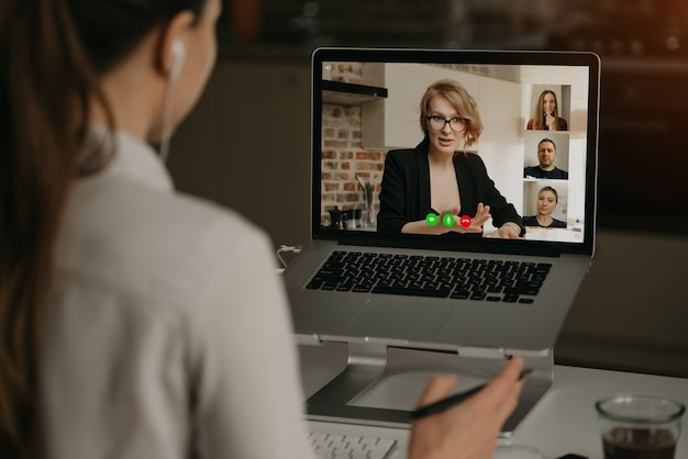 Back view of a woman at home talking with her boss and other colleagues in a video call on a laptop. businesswoman talks with coworkers on a webcam conference. business team having an online meeting.