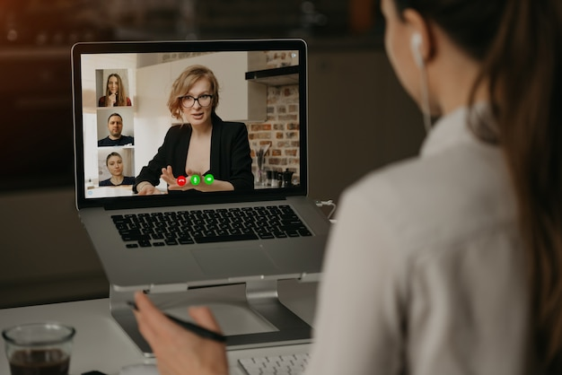 Back view of a woman at home talking with her boss and other colleagues in a video call on a laptop. businesswoman talks with coworkers on a webcam conference.