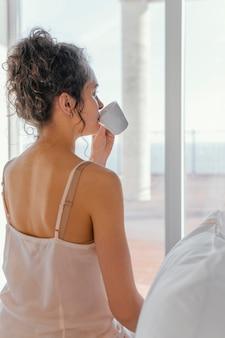 Вид сзади женщина в пижаме, пить кофе