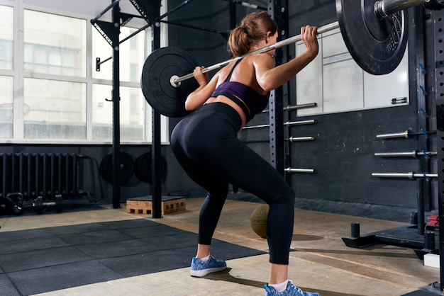 Back view of woman in lifting barbell