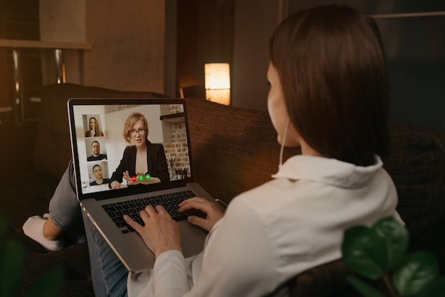 Back view of a woman lying at home on a sofa talking with her boss and other colleagues in a video call on a laptop. businesswoman talks with coworkers on a webcam conference. a team having a meeting.