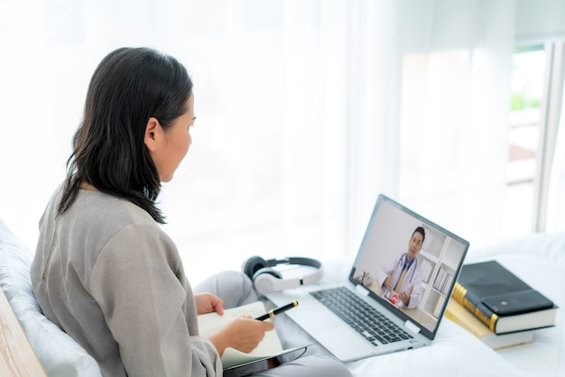 Back view of woman making video call with her doctor with her feeling sick