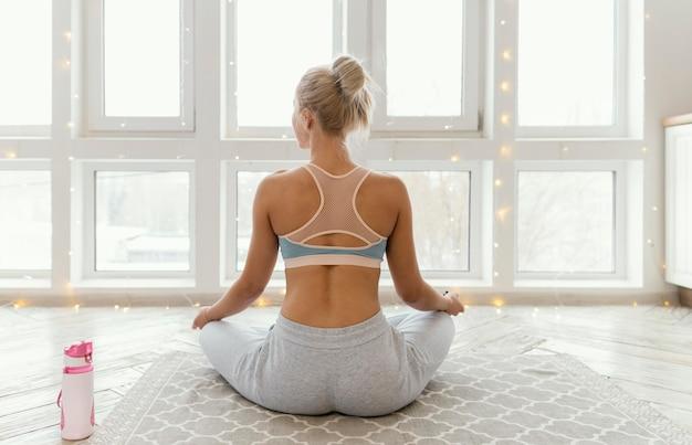 Back view woman on mat meditating