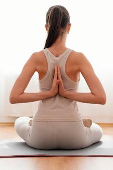 Donna di vista posteriore meditando a casa