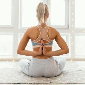 Вид сзади женщина на коврике медитирует