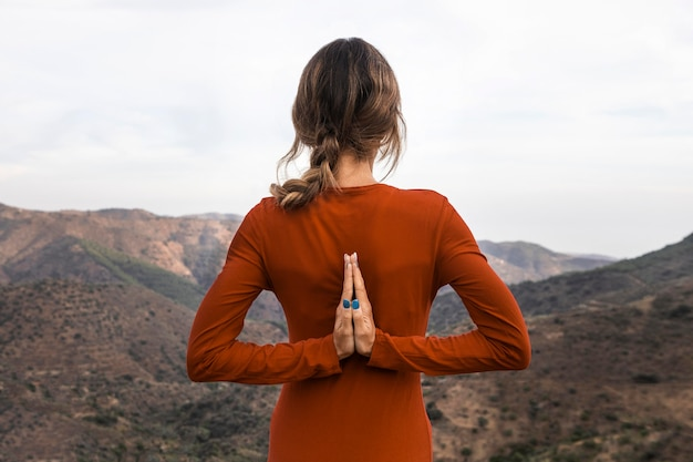 Back view of woman outdoors in nature in yoga pose