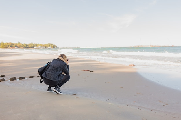 Back view of woman photographing sea with camera or smartphone while standing against copy space sea and sky background