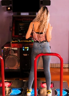 Back view woman playing dancing arcade