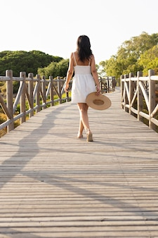 Back view of woman posing on bridge in nature