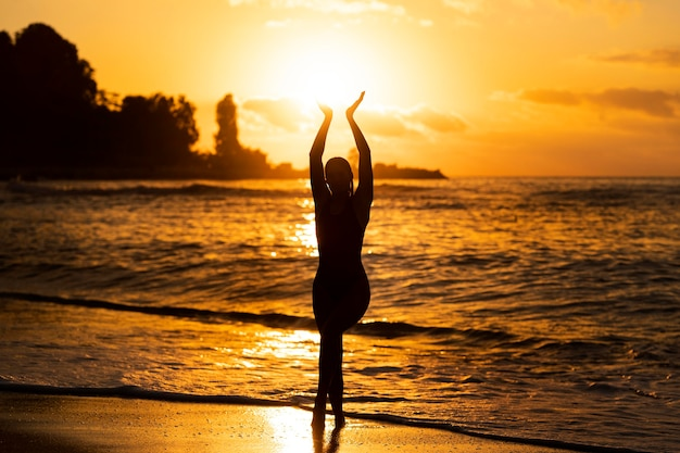 Вид сзади женщина позирует на восходе солнца