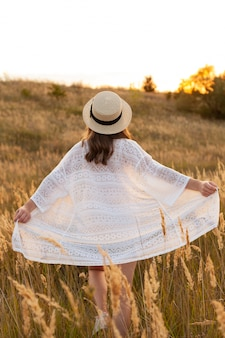 Back view of woman posing outdoors in the fields