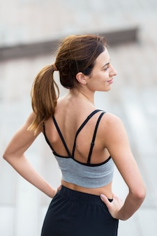 Back view of woman posing outdoors while exercising