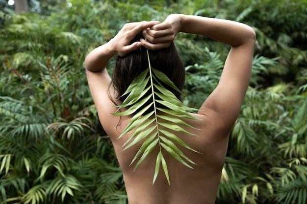 葉でポーズをとって背面図の女性
