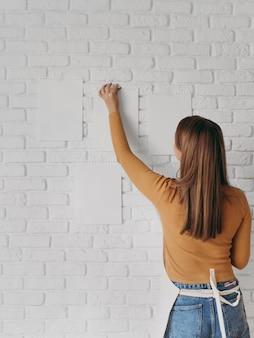 壁に紙を置く背面図の女性