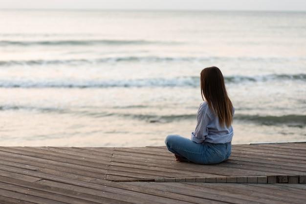Donna vista posteriore rilassante vicino al mare