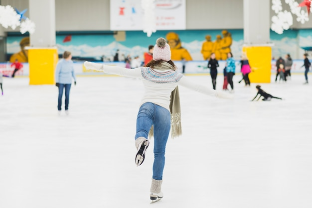 Back view woman skating on one leg