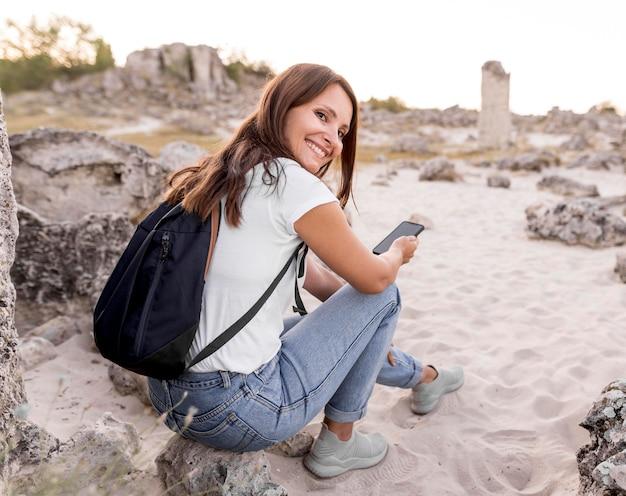Donna di vista posteriore che sorride e che si siede su una roccia