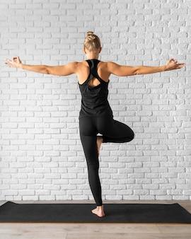 片足で立っている背面図の女性