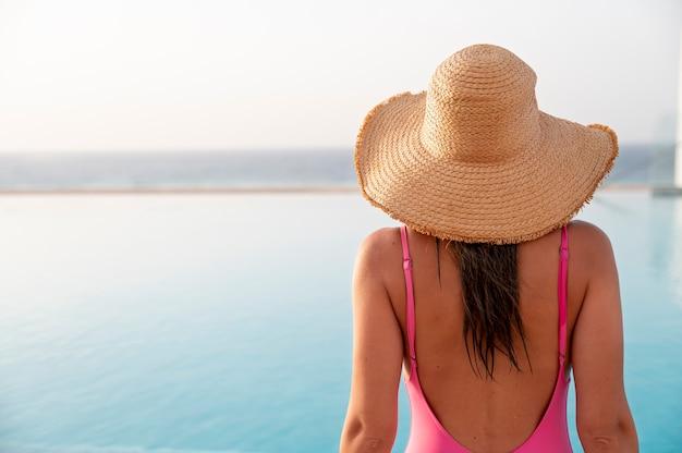 プールに立っている背面図の女性
