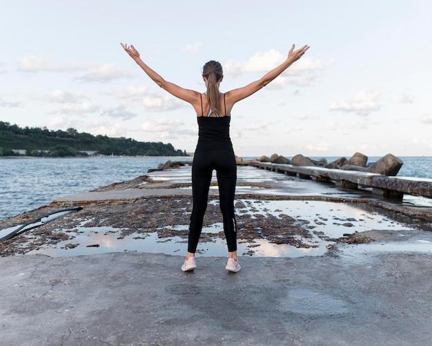 Вид сзади женщина, стоящая на палубе