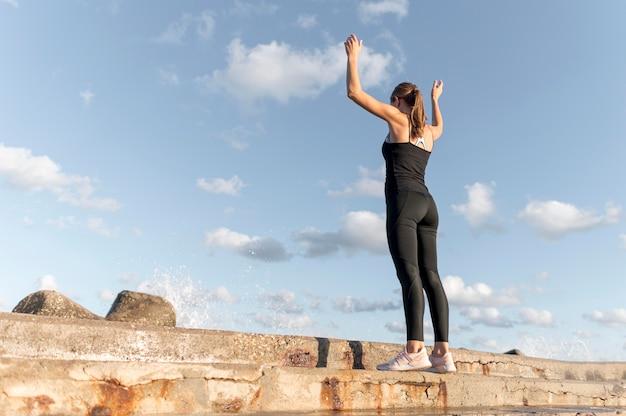 コピースペースとビーチでストレッチ女性の背面図