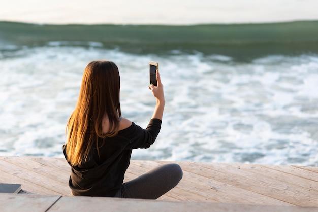 Donna di vista posteriore che cattura una foto del mare