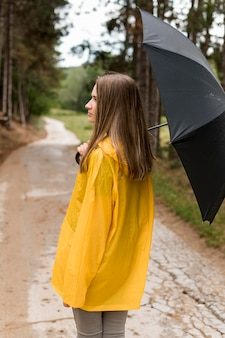 Back view woman taking a walk in the forest while holding an umbrella