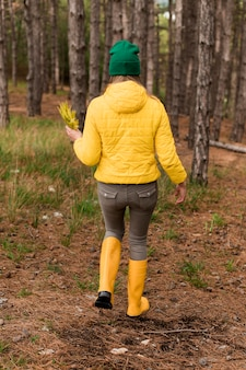 Back view woman taking a walk in the forest