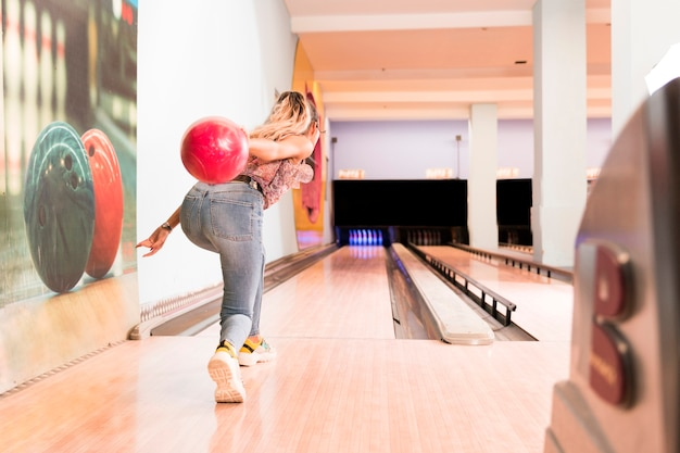 Back view woman throwing bowling ball