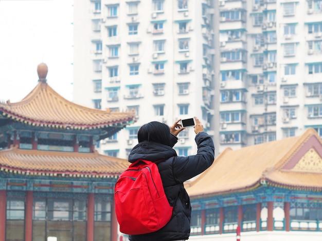 Вид сзади женщина турист фотографировать с смартфона над китайским зданием