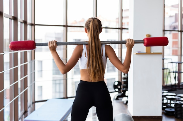 Back view of woman training with weights bar