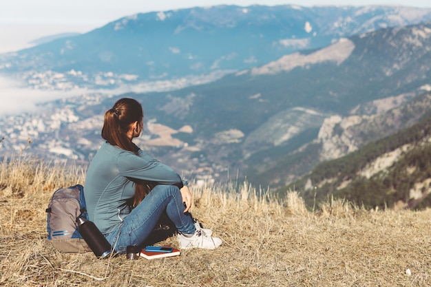 Back view of woman travel. young beautiful girl travels alone in the mountains in spring or autumn, sits on the edge of the mountain and looks into the distance